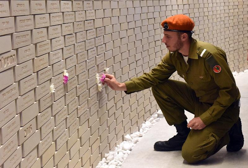 An Israeli soldier places a flower on the name of a fallen soldier in Jerusalem on April 18, 2018