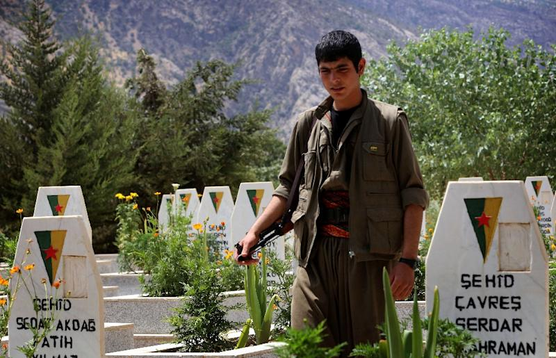 A member of the Kurdistan Workers' Party (PKK) walks past graves at a cemetary on July 29, 2015 deep in the Qandil mountain, the PKK headquarters in northern Iraq