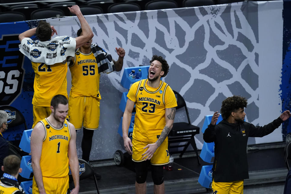 Michigan forward Brandon Johns Jr. (23) celebrates with teammates at the end of a Sweet 16 game against Florida State in the NCAA men's college basketball tournament at Bankers Life Fieldhouse, Sunday, March 28, 2021, in Indianapolis. Michigan won 76-58. (AP Photo/Darron Cummings)