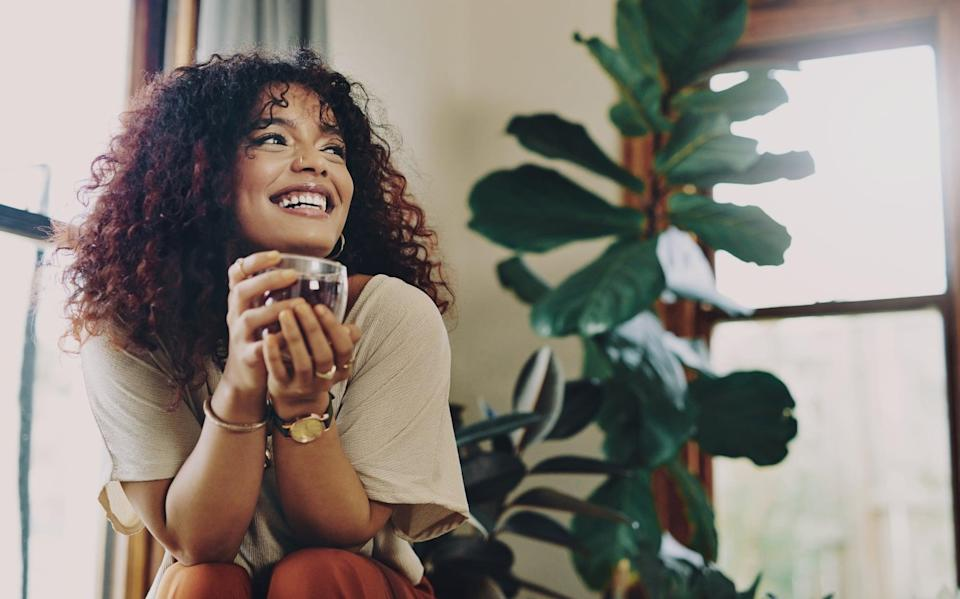 Cropped shot of an attractive young woman drinking tea while relaxing at home