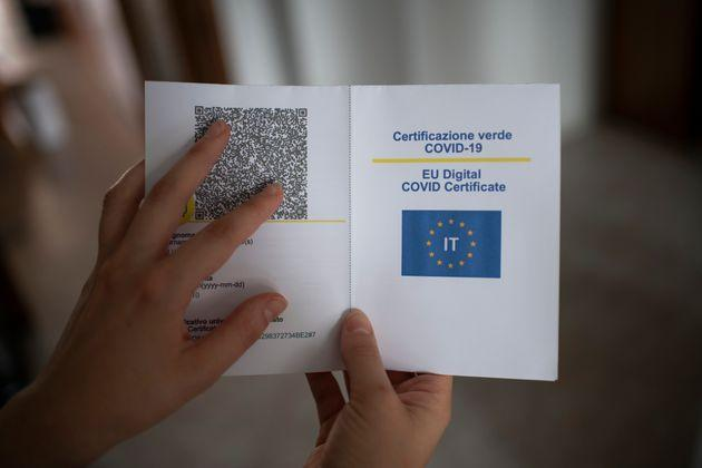 TURIN, ITALY - AUGUST 07: In this photo illustration,  the hands of a woman shows the Covid-19 Green Pass for travel on paper format on August 07, 2021 in Turin, Italy. The Italian government has approved a new rule concerning measures relating to the need to have a green pass if people want to sit at a table inside bars and restaurants and to access cinemas, theatre, museums and gyms. (Photo illustration by Stefano Guidi/Getty Images) (Photo: Stefano Guidi via Getty Images)