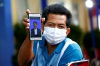 Sugiarto shows a photo of his nephew Rion Yogatama, a victim of Sriwijaya Air Flight SJ 182 that crashed into the sea off the Jakarta coast, in Indonesia