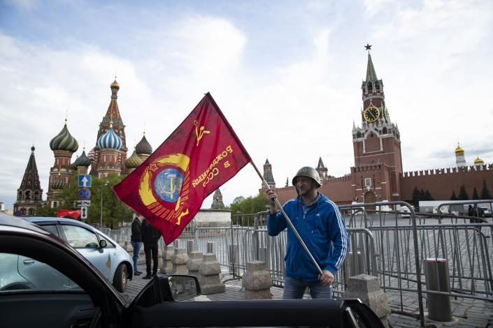 A man poses for a photo with a red flag in front of the closed Red Square during the 75th anniversary of the Nazi defeat in World War II in Moscow, Russia, Saturday, May 9, 2020. Victory Day is Russia's most important secular holiday and this year's observance had been expected to be especially large because it is the 75th anniversary, but the Red Square military parade and a mass procession called The Immortal Regiment were postponed as part of measures to stifle the spread of coronavirus. (AP Photo/Pavel Golovkin)