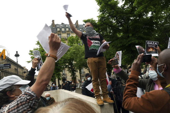 A protester distributes leaflets during a protest in solidarity with Palestinians, in Paris, Wednesday, May 12, 2021. (AP Photo/Thibault Camus)