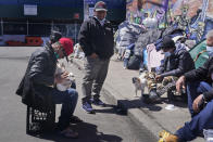 Sotero Cirilo, left, and Alfredo Martinez, second from left, relax in front of the tents where they have been sleeping in the Queens borough of New York, Tuesday, April 13, 2021. Unemployment among Hispanic immigrants has doubled in the U.S., going from 4.8% in January 2020 to 8.8% in February 2021, according to the Migration Policy Institute. (AP Photo/Seth Wenig)