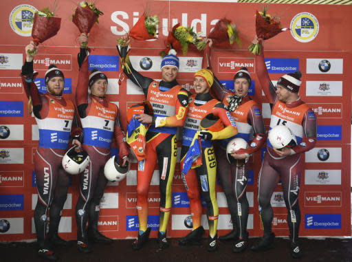 From left, Oskars Gudramovics and Peteris Kalnins of Latvia, second place, Toni Eggert and Sascha Benecken of Germany, first place, Andris Sics and Juris Sics of Latvia, third place, celebrate on the podium after their men's doubles race at the Luge World Cup event in Sigulda, Latvia, Saturday, Jan. 12, 2019. (AP Photo/Roman Koksarov)