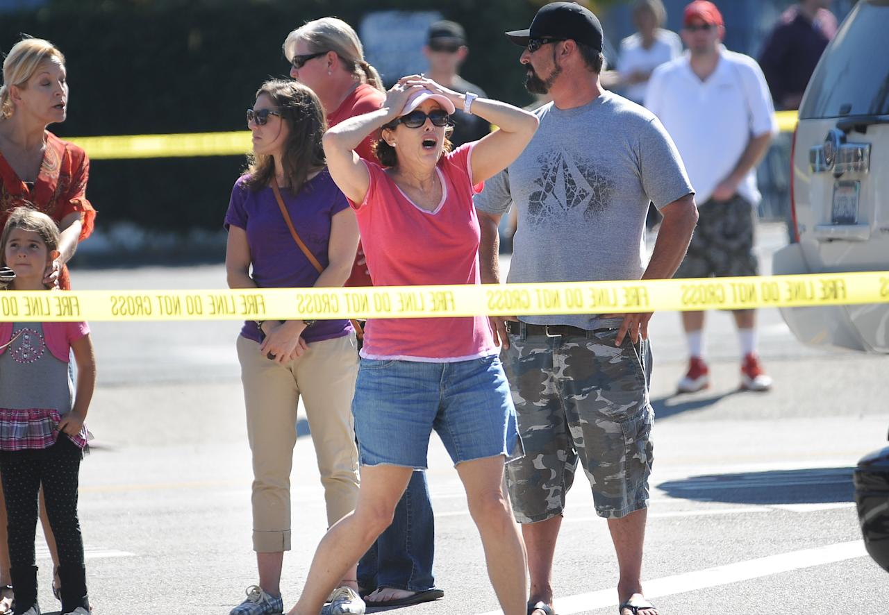 Onlookers react near the site where six people were killed and three were wounded in a shooting at a hair salon in Seal Beach, Calif., Wednesday, Oct. 12, 2011. The six deaths were confirmed and the other three victims were taken to a hospital in critical condition, police Sgt. Steve Bowles told The Associated Press. (AP Photo/The Daily Breeze, Stephen Carr) MAGS OUT; NO SALES