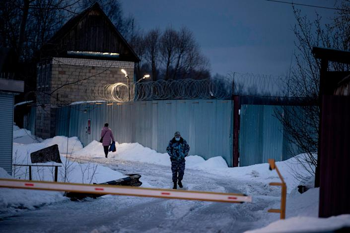"""An officer of the Russian Federal Penitentiary Service walks near the gate of the penal colony N2, where the Kremlin critic has been transferred to serve out a prison term, in the town of Pokrov on March 1, 2021.<span class=""""copyright"""">Dimitar Dilkoff—AFP/Getty Images</span>"""