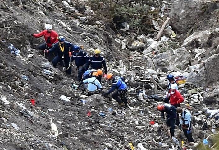 French gendarmes and investigators work in the scattered debris at the crash site of the Germanwings Airbus A320 in the French Alps, on March 26, 2015 (AFP Photo/Anne-Christine Poujoulat)