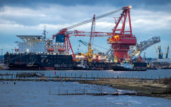 """FILE - In this Jan. 14, 2021 file photo, Tugboats get into position on the Russian pipe-laying vessel """"Fortuna"""" in the port of Wismar, Germany, Thursday, Jan 14, 2021. The special vessel is being used for construction work on the German-Russian Nord Stream 2 gas pipeline in the Baltic Sea. The company building a disputed Russian-German subsea pipeline says work on the gas pipeline has resumed, the German news agency dpa reports. Construction on the Nord Stream 2 pipeline was resumed late Saturday, dpa reported Sunday. ( Jens Buettner/dpa via AP, File) - Jens Buettner/DPA"""