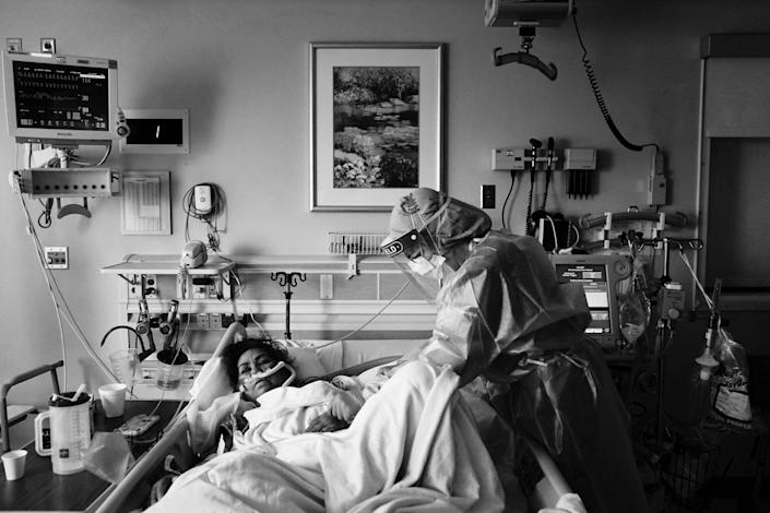 Registered nurse Merri Lynn Anderson, right, tends to her patient in a COVID-19 unit at St. Joseph Hospital in Orange, Calif., Thursday, Jan. 7, 2021.