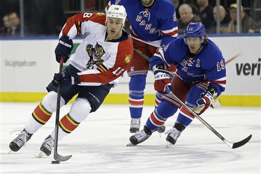 Florida Panthers' Shawn Matthias (18) moves the puck as New York Rangers' Brad Richards (19) skates in during the first period of an NHL hockey game Thursday, March 21, 2013, in New York. (AP Photo/Frank Franklin II)