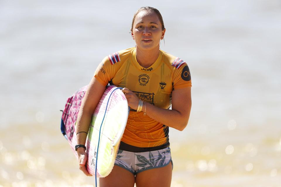 Carissa Moore carrying her surfboard