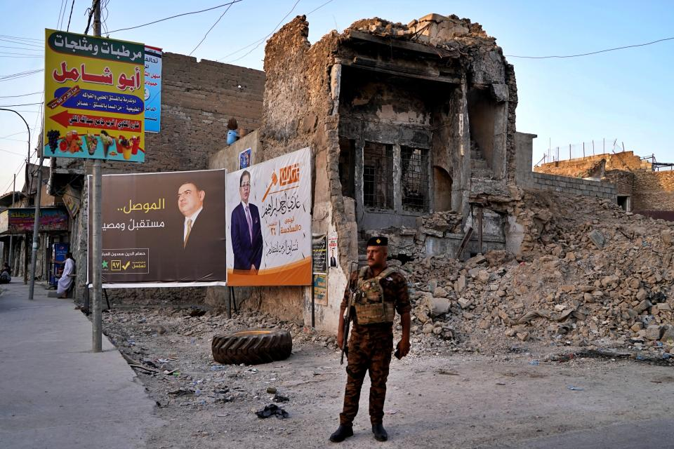 An Iraqi federal policeman stands guard near campaign posters for parliamentary elections are displayed near destroyed buildings from fighting between Iraqi forces and the Islamic State group in Mosul, Iraq, Sunday, Oct. 3, 2021. Iraq on Sunday, Oct. 10, holds its fifth election since the 2003 U.S.-led invasion that toppled Iraqi dictator Saddam Hussein, with most Iraqis longing for real change. (AP Photo)