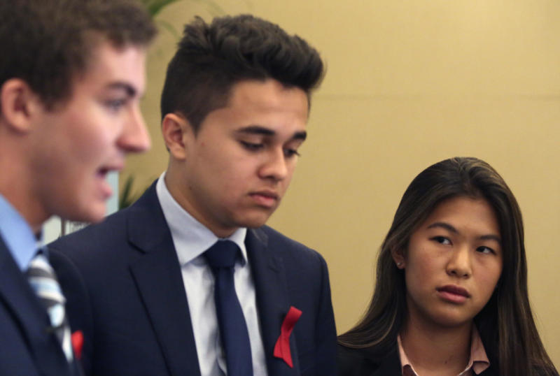 Parkland High School students Lewis Mizen, left, Kevin Trejos, center, and Suzanna Barna, right, speak to The Associated Press in Dubai, United Arab Emirates, Saturday, March 17, 2018. Student survivors of a Florida high school shooting took their message calling for greater gun safety measures abroad for the first time on Saturday, sharing with educational professionals from around the world their frightening experience. (AP Photo/Jon Gambrell)