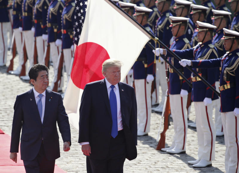 FILE - In this Nov. 6, 2017, file photo, U.S. President Donald Trump, second left, reviews an honor guard during a welcome ceremony, escorted by Japanese Prime Minister Shinzo Abe at Akasaka Palace in Tokyo. Trump will make a state visit to Japan at the end of May, 2019 to meet the nation's new emperor. (AP Photo/Koji Sasahara, Pool, File)