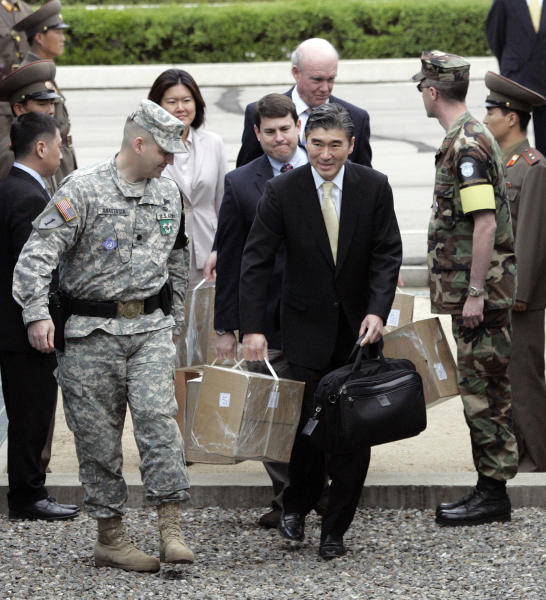 FILE- In this May 10, 2008, file photo, then U.S. State Department's top Korea specialist Sung Kim, center, and other officials cross the border as they carry box loads of documents detailing activity at North Korea's key nuclear reactor at the border village of Panmunjom in the demilitarized zone that separates the two Koreas, South Korea. The success of the second summit between President Donald Trump and North Korean leader Kim Jong Un hinges largely on whether Kim proves he's truly committed to denuclearization. (AP Photo/ Lee Jin-man, File)