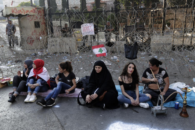 Anti-government protesters sit in front of a barbed-wire barrier on a road that leads to the Government House, during a protest in Beirut, Lebanon, Tuesday, Oct. 22, 2019. Prime Minister Saad Hariri briefed western and Arab ambassadors Tuesday of a reform plan approved by the Cabinet that Lebanon hopes would increase foreign investments to help its struggling economy amid wide skepticism by the public who continued in their protests for the sixth day. (AP Photo/Hassan Ammar)