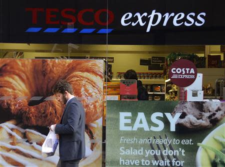 A customer passes a branch of the Tesco Express convenience store in central London December 12, 2013. REUTERS/Toby Melville