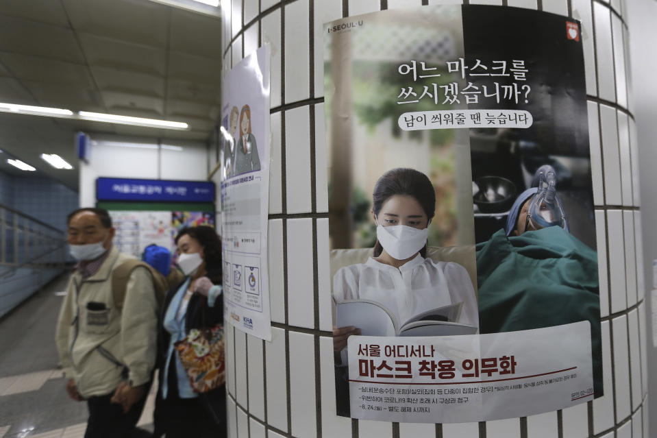 "People wearing face masks to help protect against the spread of the coronavirus walk by a poster informing mandatory mask wearing at a subway station in Seoul, South Korea, Sunday, Sept. 20, 2020. South Korea's new coronavirus tally has fallen below 100 for the first time in more than a month. The banner reads: "" Which mask would you wear?"" (AP Photo/Ahn Young-joon)"
