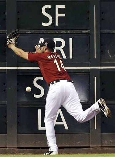 Houston Astros left fielder J.D. Martinez runs into the outfield wall while trying to catch a double hit by Philadelphia Phillies' Michael Martinez during the seventh inning of a baseball game, Sunday, Sept. 16, 2012, in Houston. (AP Photo/David J. Phillip)