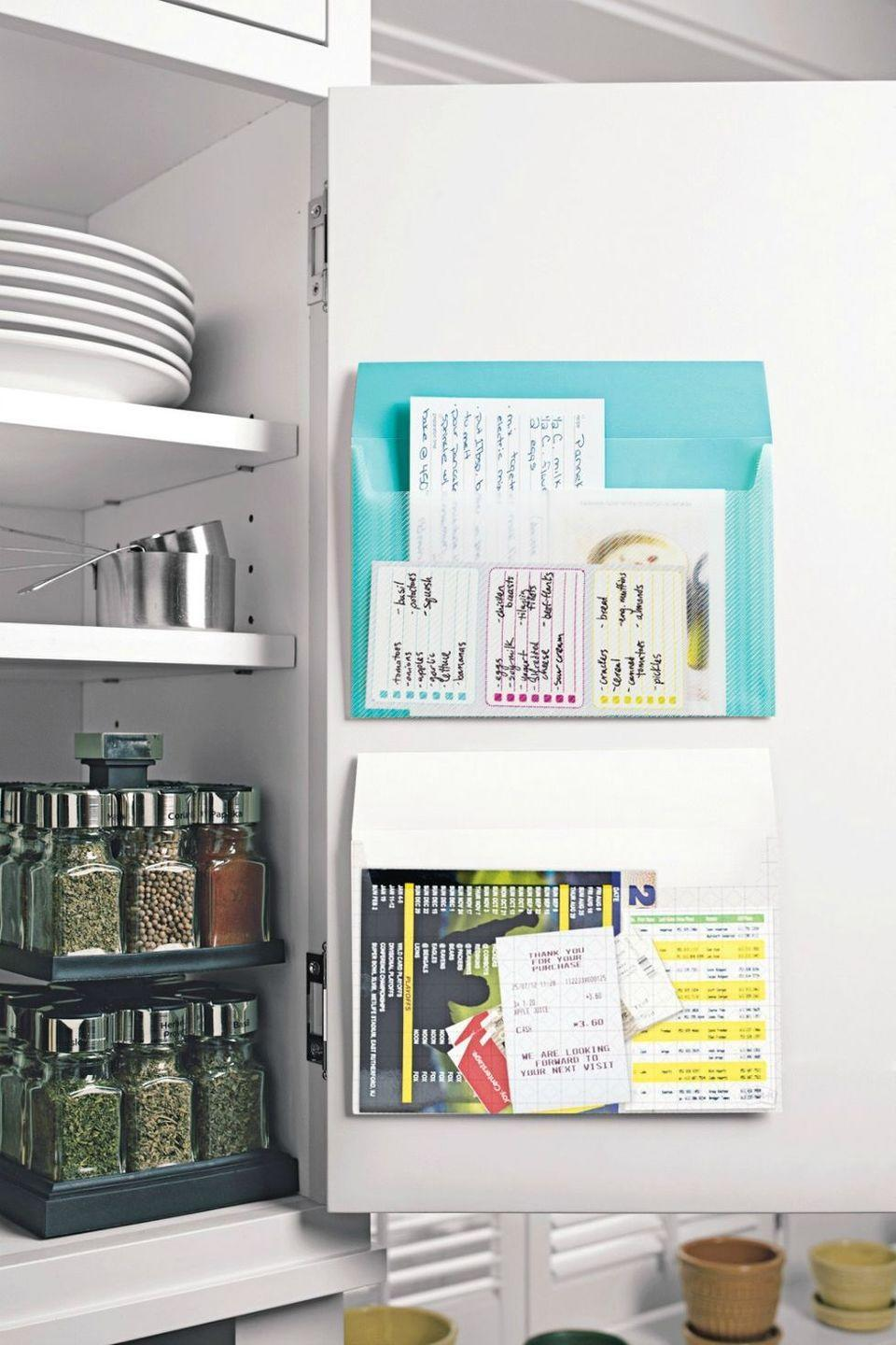 <p>Stick adhesive pockets to the inside of your spice cabinet to keep all of your grocery lists, coupons, and recipes in one spot. Add a pen loop, so you don't have to go searching to jot something down. <br></p>