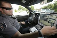 Office Dennis Vafier of the Alexandria Police Dept., uses a laptop in his squad car to scan vehicle license plates during his patrols, Tuesday, July 16, 2013 in Alexandria, Va. Local police departments across the country have amassed millions of digital records on the location and movements of vehicles with a license plate using automated scanners. Affixed to police cars, bridges or buildings, the scanners capture images of passing or parked vehicles and note their location, dumping that information into police databases. Departments keep the records for weeks or even years. (AP Photo/Pablo Martinez Monsivais)