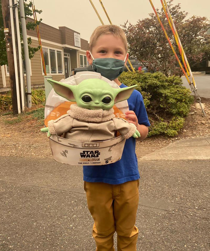 Five-year-old Carver holds up a Baby Yoda toy in Scappoose, Oregon. Carver donated the toy to Oregon firefighters, who have been having fun posing the tiny green Force user on the fire lines since. (Courtesy of Tyler Eubanks) (Tyler Eubanks / AP)