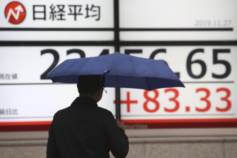 A man walks by an electronic stock board of a securities firm in Tokyo, Wednesday, Nov. 27, 2019. Shares were mostly higher in Asia on Wednesday after a fresh set of record highs on Wall Street, spurred by encouraging signs on trade talks between the U.S. and China. (AP Photo/Koji Sasahara)