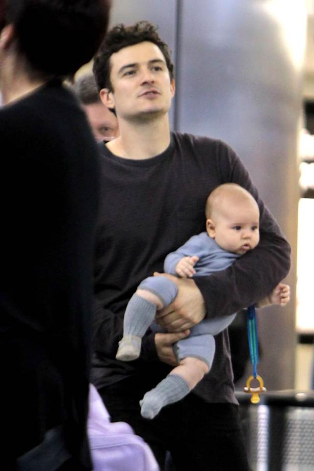 """Safely ensconced in the arms of his daddy Orlando Bloom -- and with his pacifier securely pinned to his jumpsuit -- 3-month-old Flynn was all ready to jet when spotted at Los Angeles International Airport Monday. How adorable are those chubby cheeks? <a href=""""http://www.splashnewsonline.com"""" target=""""new"""">Splash News</a> - April 18, 2011"""