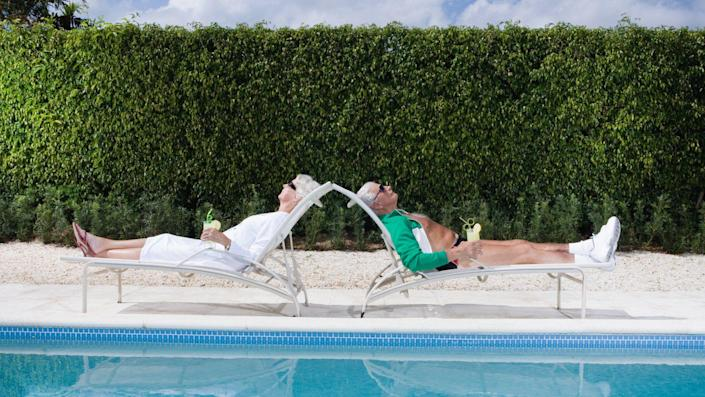 Caucasian, Drink, Drinking Glass, Female, GARDEN, Life, Lounge Chair, Male, Summer, Sunbathing, Swimming Pool, back to back, color, hedge, heterosexual couple, holding, horizontal, husband, leisure, longevity, man, outdoor, photography, poolside, reclining, relaxation, retirement, senior adult, senior man, senior woman, sitting, two people, vacation, wife, woman