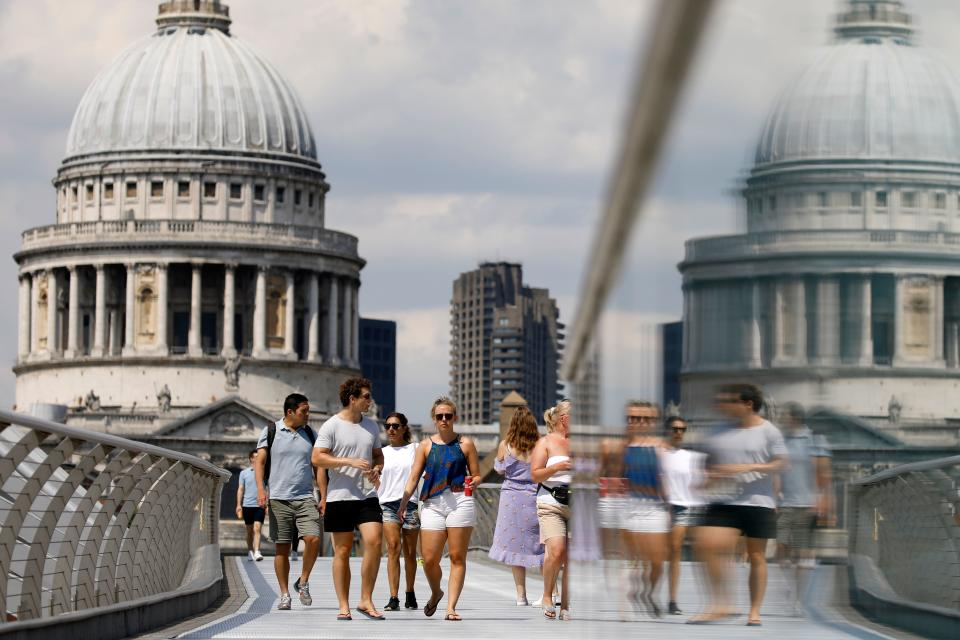 People walk over The Millennium Bridge away from St Paul's Cathedral in London on June 26, 2020, as temperatures are expected to again be high, hitting 31 degrees Celsius in London. - Britons were on Friday urged to abide by social distancing rules over fears over a coronavirus resurgence after tens of thousands of people descended on beaches during a heatwave. (Photo by Tolga AKMEN / AFP) (Photo by TOLGA AKMEN/AFP via Getty Images)