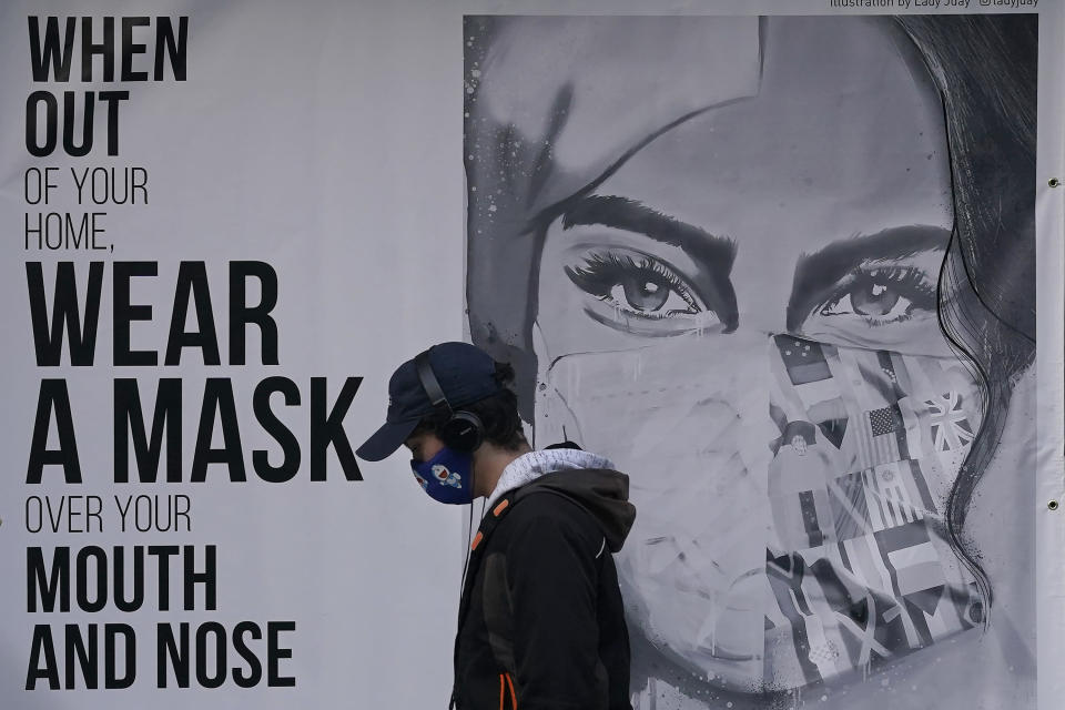 """FILE - In this Nov. 21, 2020, file photo, a pedestrian walks past a mural reading: """"When out of your home, Wear a mask over your mouth and nose,"""" during the coronavirus outbreak in San Francisco. From speculation that the coronavirus was created in a lab to a number of hoax cures, an overwhelming amount of false information about COVID-19 has followed the virus as it circled the globe over the past year. (AP Photo/Jeff Chiu, File)"""