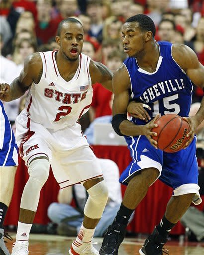 UNC Asheville's Jeremy Atkinson (15) battles with North Carolina State's Lorenzo Brown (2) during the first half of an NCAA college basketball game in Raleigh, N.C., Friday, Nov. 23, 2012. (AP Photo/Karl B DeBlaker)