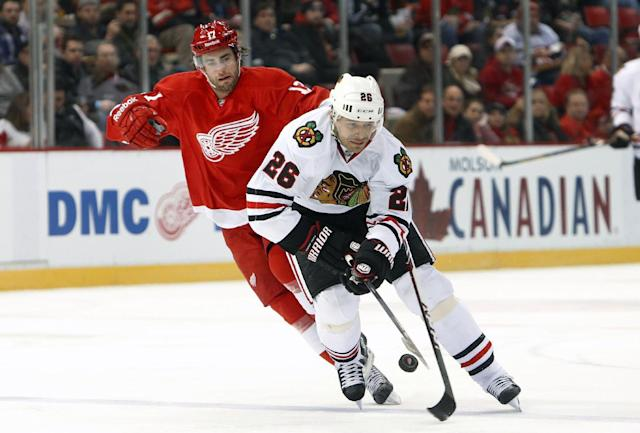 Chicago Blackhawks center Michal Handzus (26), of Czech Republic, tries to control the puck as Detroit Red Wings right wing Patrick Eaves defends in the first period of an NHL hockey game Wednesday, Jan. 22, 2014, in Detroit. (AP Photo/Paul Sancya)