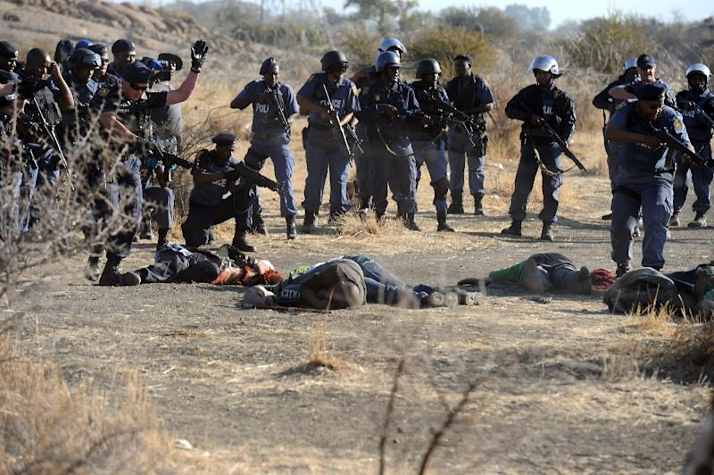 Police surround fallen miners after they opened fire during clashes near a platinum mine in Marikana on August 16, 2012 (AFP Photo/)