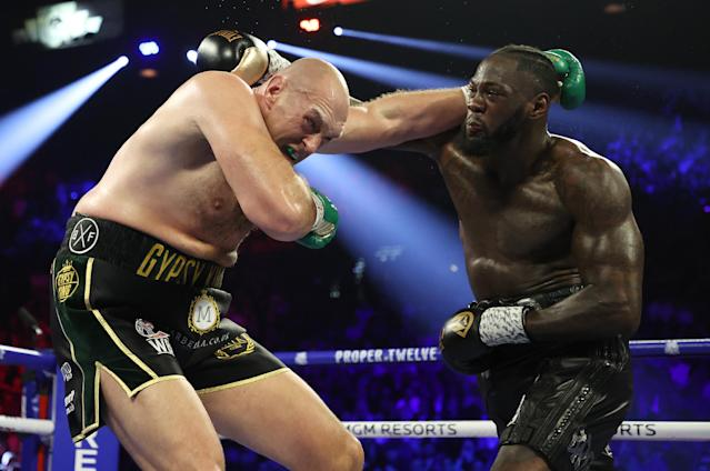 Deontay Wilder (R) and Tyson Fury battle during their heavyweight title bout on Feb. 22 at the MGM Grand Garden in Las Vegas. Wilder on Friday exercised a rematch clause and will meet Fury for a third time later this year. (Photo by Al Bello/Getty Images)
