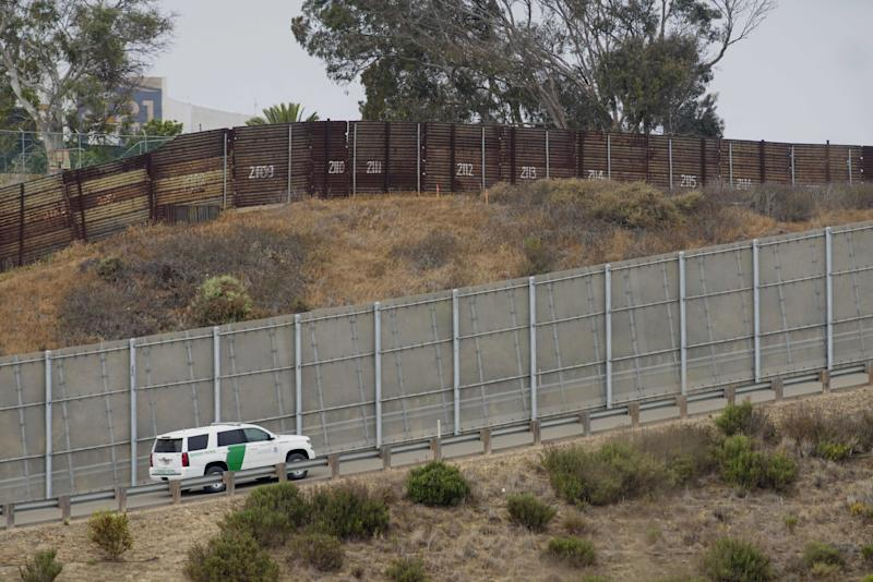 A Border Patrol car drives past the old border wall just east of where construction is set to begin on new fencing in San Ysidro, California.