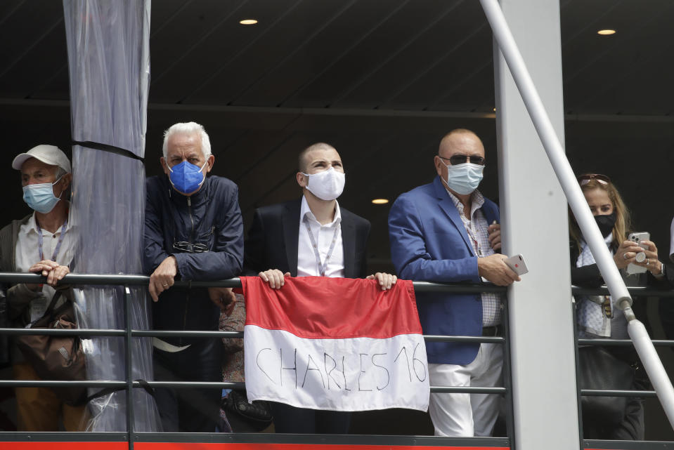 Spectators stand on a balcony with a flag to cheer on Ferrari driver Charles Leclerc of Monaco prior to the Monaco Grand Prix at the Monaco racetrack, in Monaco, Sunday, May 23, 2021. (AP Photo/Luca Bruno)