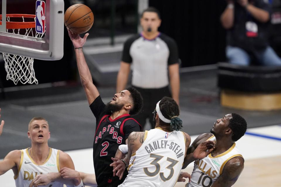 Toronto Raptors guard Jalen Harris (2) goes up for a shot after getting though the defense of Dallas Mavericks' Kristaps Porzingis, left, Willie Cauley-Stein (33) and Dorian Finney-Smith (10) in the second half of an NBA basketball game in Dallas, Friday, May 14, 2021. (AP Photo/Tony Gutierrez)