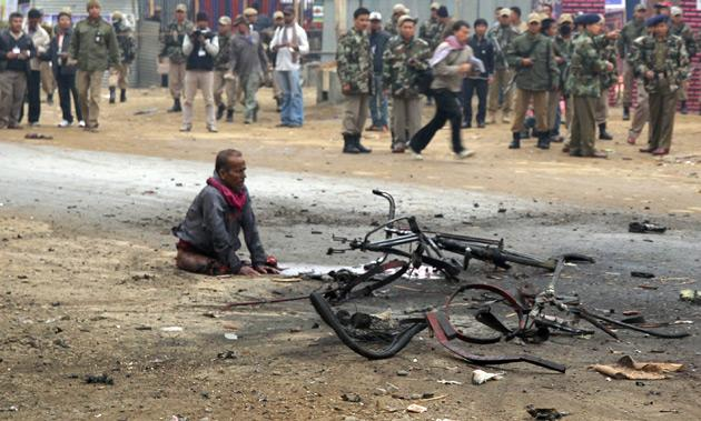 An injured rickshaw puller, who later died from his injuries, is seen at the site of a bomb blast as security personnel look on in the northeastern Indian city of Imphal November 30, 2011. Two people were injured and one died after a bomb exploded at the entrance of a ten-day-long tourism festival, local media reported on Wednesday. REUTERS/Stringer