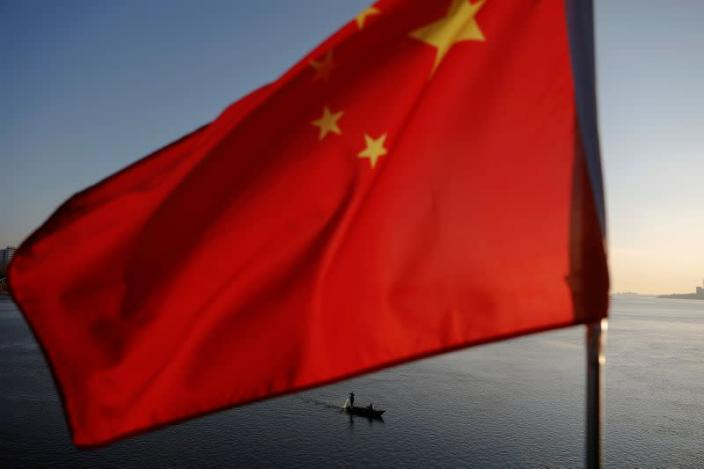 FILE PHOTO: North Korean fishermen are seen behind a Chinese flag fluttering from the Broken Bridge as the sun sets over the Yalu River between the North Korean town of Sinuiju and Dandong in Liaoning province