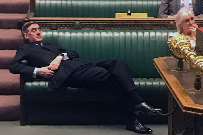 Flat out: Jacob Rees-Mogg lies back on the green benches of the House during the debate over the Commons timetable (AFP/Getty Images)