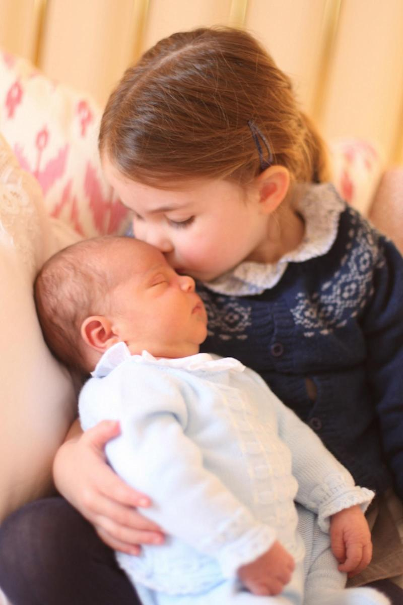 Princess Charlotte plants a kiss on her newborn baby brother Prince Louis in this adorable snap taken by their mother (PA)