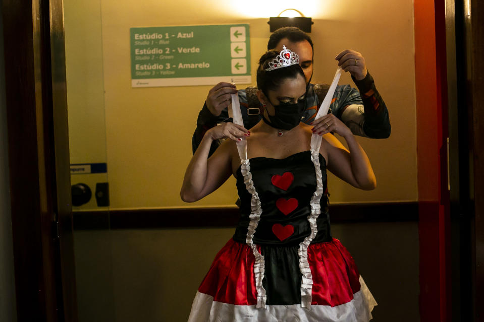 """Members of the """"Desliga da Justica"""" street band get dressed in their costumes in Rio de Janeiro, Brazil, Sunday, Feb. 14, 2021. Their performance was broadcast live on social media for those who were unable to participate in the carnival due to COVID restrictions after the city's government officially suspended Carnival and banned street parades or clandestine parties. (AP Photo/Bruna Prado)"""