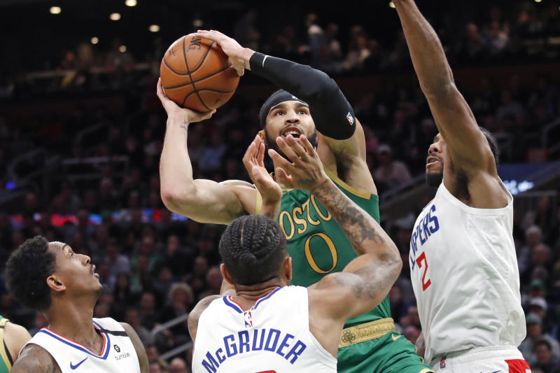 Boston Celtics forward Jayson Tatum (0) goes up to shoot against Los Angeles Clippers', from left to right, Lou Williams, Rodney McGruder and Kawhi Leonard in the first half of an NBA basketball game, Thursday, Feb. 13, 2020, in Boston. (AP Photo/Elise Amendola)