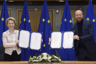 European Commission President Ursula von der Leyen, left, and European Council President Charles Michel show signed EU-UK Trade and Cooperation Agreement at the European Council headquarters in Brussels, Wednesday, Dec. 30, 2020. European Union's top officials have formally signed the post-Brexit trade deal sealed with the United Kingdom. European Commission president Ursula von der Leyen and European Council president Charles Michel put pen to paper on Wednesday morning during a brief ceremony in Brussels (Johanna Geron, Pool Photo via AP)