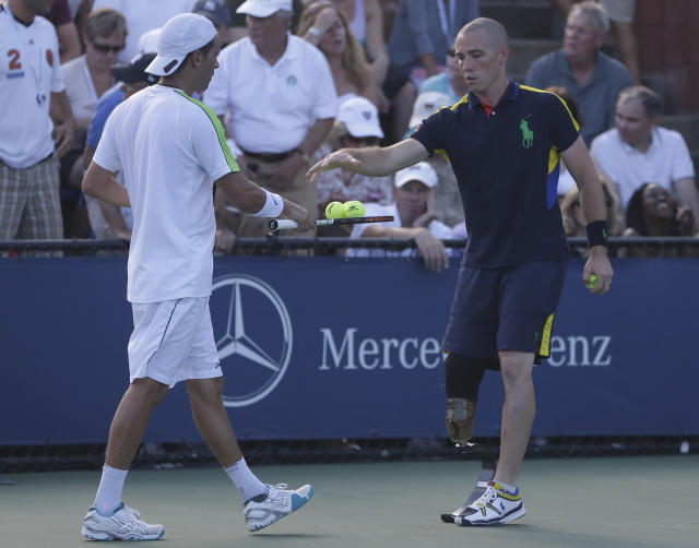 Ryan McIntosh, right, takes the extra balls from Albert Montanes of Spain while working a match in the second round of play at the 2012 US Open tennis tournament, Wednesday, Aug. 29, 2012, in New York. (AP Photo/Darron Cummings)