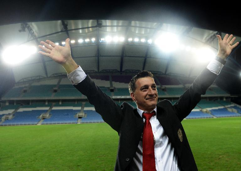 Gibraltar's head coach Allen Bula gestures to supporters at the end of the World Cup 2014 friendly football match against Slovakia at Algarve stadium in Faro on November 19, 2013