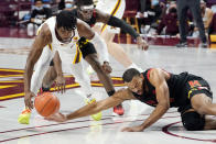 Minnesota's Marcus Carr, left, and Maryland's Donta Scott, right, reach for a loose ball in the first half of an NCAA college basketball game, Saturday, Jan. 23, 2021, in Minneapolis. (AP Photo/Jim Mone)